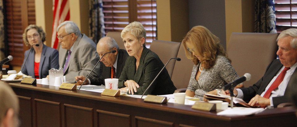 Photo - State schools Superintendent Janet Barresi, center, makes comments Thursday during a meeting of the Oklahoma Board of Education at the state Capitol in Oklahoma City.  Photos by Paul B. Southerland, The Oklahoman  PAUL B. SOUTHERLAND