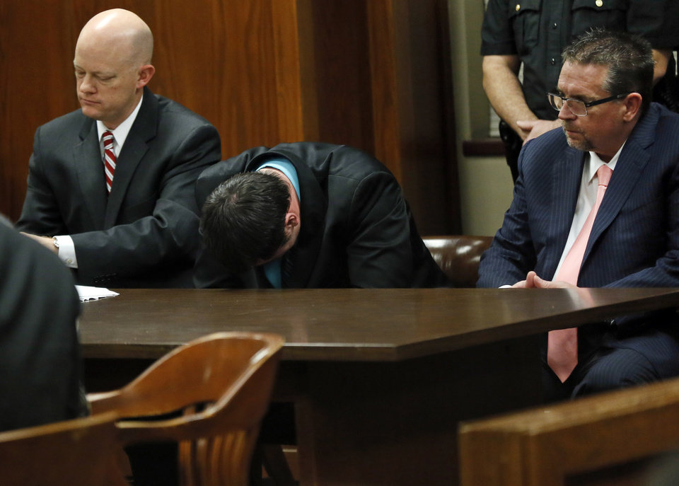 Photo - Former Oklahoma City police officer Daniel Holtzclaw rocks back and forth with his head down between attorneys Robert Gray, left, and Scott Adams as the verdicts are read at the Oklahoma County Courthouse in Oklahoma City, Thursday, Dec. 10, 2015. Holtzclaw was found guilty of 18 of the 36 charges against him. He was accused of sexually assaulting 13 black females between December 2013 and June 2014. Photo by Nate Billings, The Oklahoman