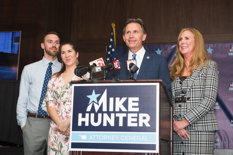 Photo - Attorney General Mike Hunter gives a speech during his watch party at the Renaissance Waterford Oklahoma City Hotel in Oklahoma City, Tuesday, June 26, 2018. He is accompanied by his wife Cheryl, right, and his son and daughter-in-law, Barrett and Rachael Hunter. Photo by Anya Magnuson, The Oklahoman