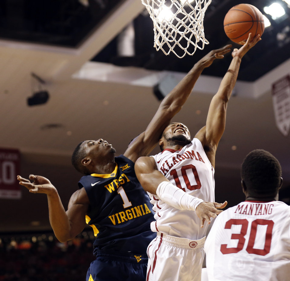 Photo - Oklahoma's Jordan Woodard (10) shoots guarded by West Virginia's Jonathan Holton (1) as the University of Oklahoma Sooner (OU) men play the West Virginia Mountaineers (WV) in NCAA, college basketball at The Lloyd Noble Center on Jan. 16, 2016 in Norman, Okla. Photo by Steve Sisney, The Oklahoman