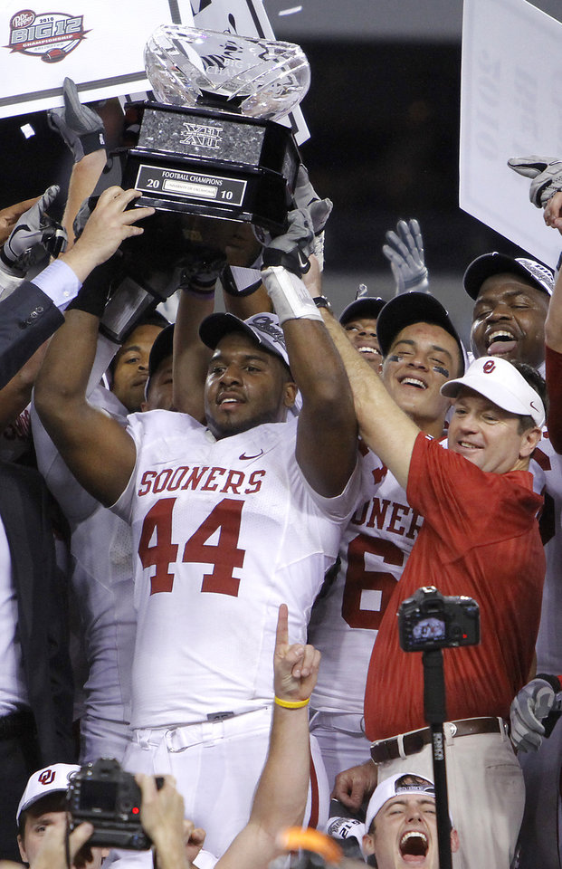 Photo - COLLEGE FOOTBALL / BIG 12 CHAMPIONSHIP: Oklahoma's Jeremy Beal and coach Bob Stoops hold up the Big 12 Championship trophy after the 23-20 win over Nebraska during the Big 12 football championship game between the University of Oklahoma Sooners (OU) and the University of Nebraska Cornhuskers (NU) at Cowboys Stadium on Saturday, Dec. 4, 2010, in Arlington, Texas.  Photo by Chris Landsberger, The Oklahoman ORG XMIT: KOD