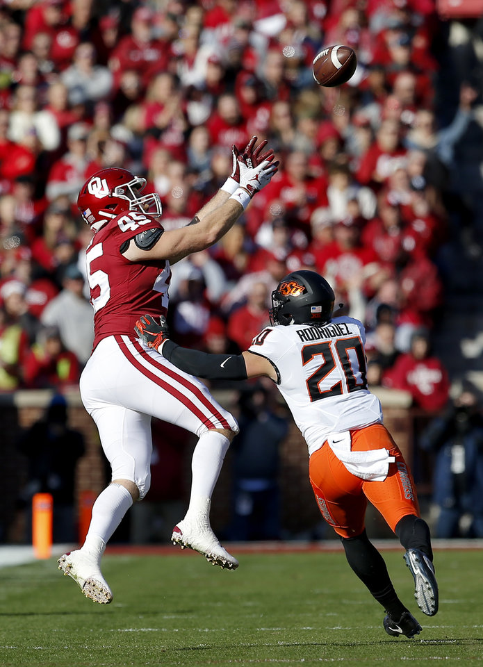 Photo - Oklahoma's Carson Meier (45) makes a reception in front of Oklahoma State's Malcolm Rodriguez (20) in the first quarter during a Bedlam college football game between the University of Oklahoma Sooners (OU) and the Oklahoma State University Cowboys (OSU) at Gaylord Family-Oklahoma Memorial Stadium in Norman, Okla., Nov. 10, 2018.  OU won 48-47. Photo by Sarah Phipps, The Oklahoman