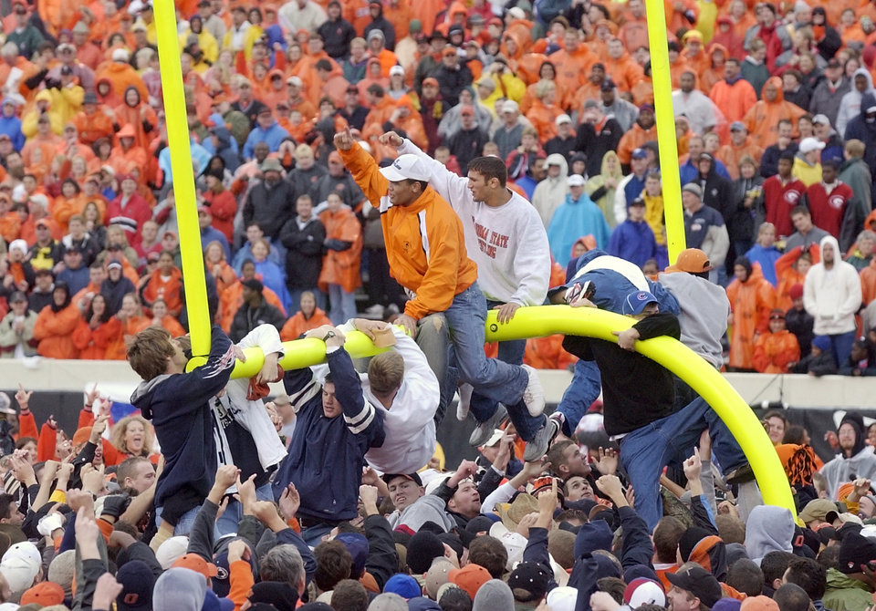 Photo - Oklahoma State vs. Nebraska college football at Lewis Field in Stillwater, Okla., Saturday, October 19, 2002. OSU fans tear down a goal post after the Cowboys beat Nebraska 24-21. Staff photo by Nate Billings.