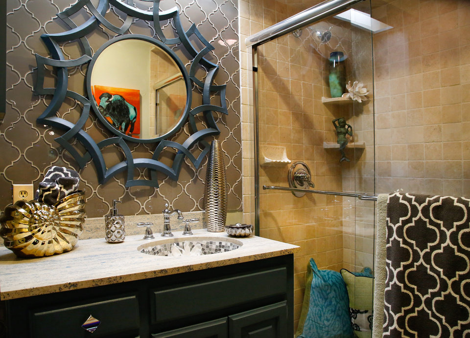 Photo - Crystal Carte, owner of Carte's Interiors in Edmond, tackled a bathroom off the Symphony Show House media room, finishing the walls in hand-cut glass tiles in shapes mirroring the metal-work motif found elsewhere in the house.   PHOTO BY JIM BECKEL, THE OKLAHOMAN  JIM BECKEL -  THE OKLAHOMAN
