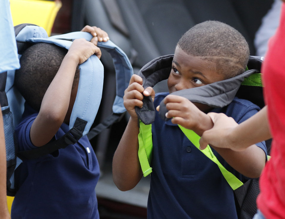 Photo - Four year old Eryk King, left and six year old Kenneth Ezell wear their new backpacks at the beginning of the first day of school at Thelma Parks Elementary School in Oklahoma City, Okla. Tuesday, Aug. 1, 2017.  Photo by Paul Hellstern, The Oklahoman