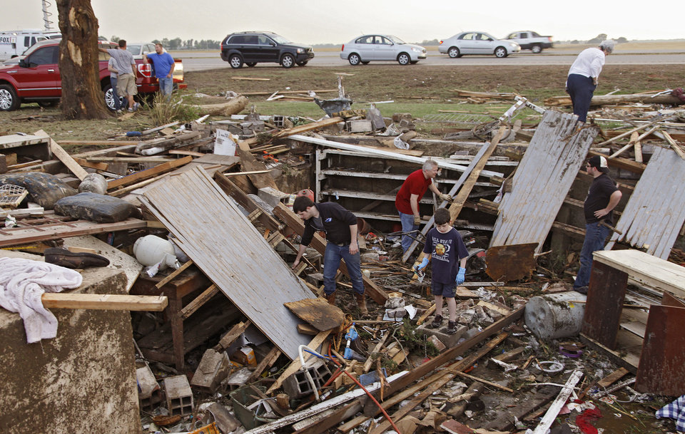 Photo - Friends and family dig through the debris left behind after a tornado destroyed the home of Tom Chronister north of El Reno, Tuesday, May 24, 2011. Photo by Chris Landsberger, The Oklahoman ORG XMIT: KOD