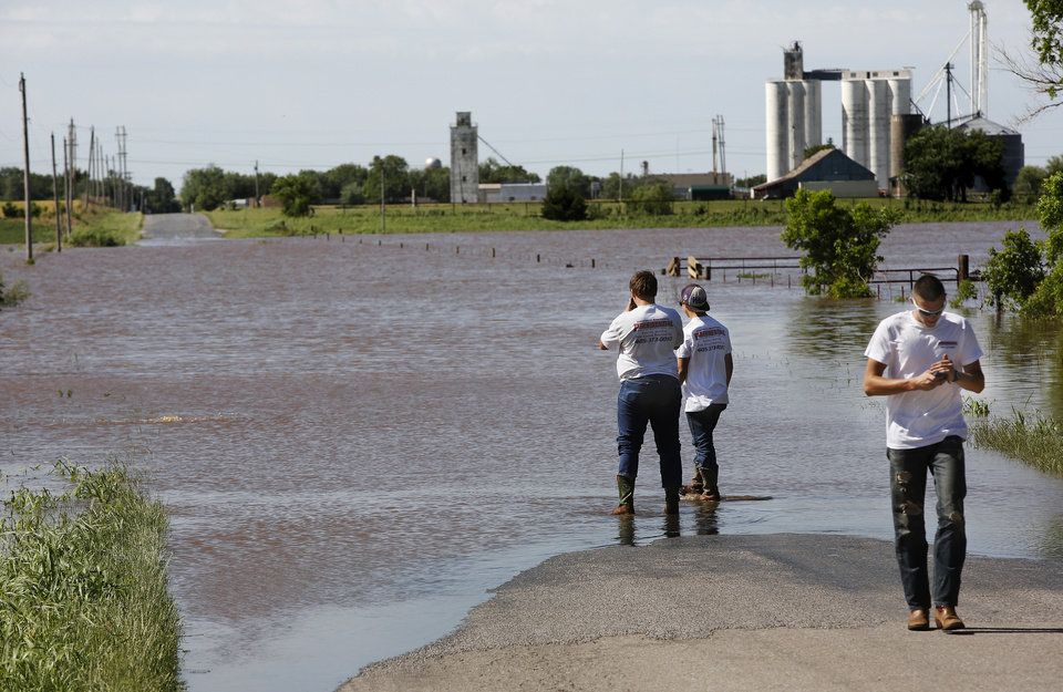 Photo - Matt Wyatt and Chase Biggs check the level of water flowing across Banner Road in El Reno as their friend, Tyler Eisenhour determines it is too deep and walks to their truck to find an alternate route to their work site on  Saturday, June 1, 2013.  Photo  by Jim Beckel, The Oklahoman.