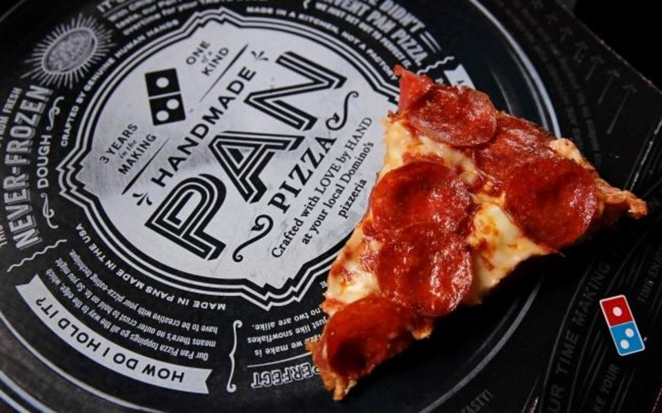 Photo -  A slice of pepperoni pizza on a Domino's Pizza box. [AP Photo/Charles Krupa, File]