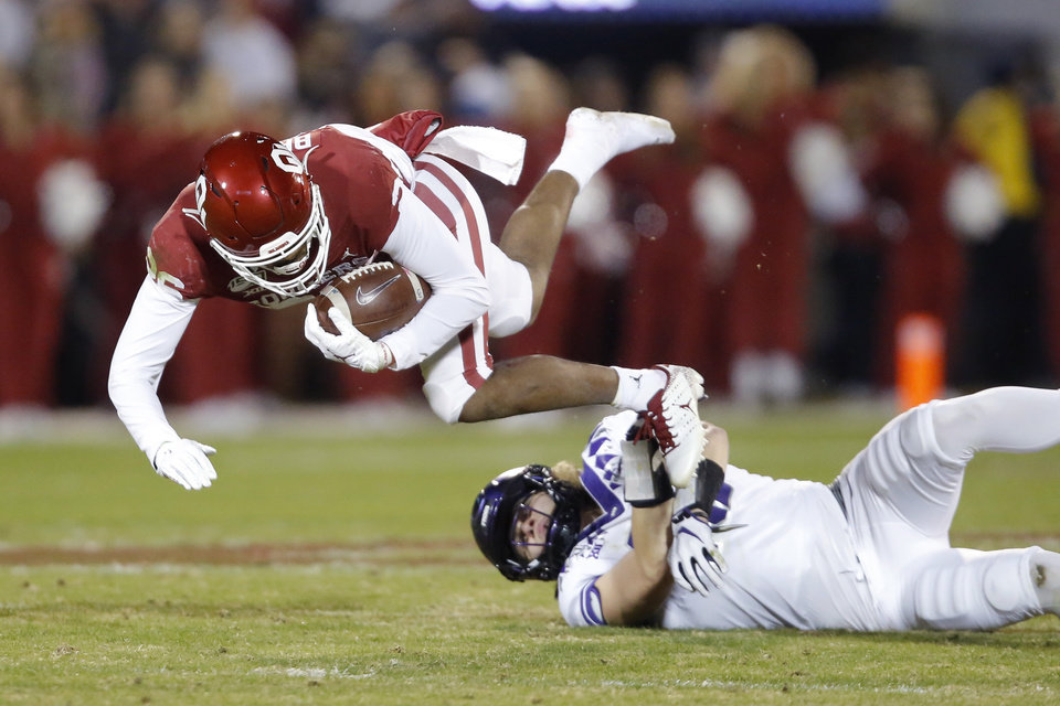 Photo - Oklahoma's Kennedy Brooks (26) is brought down by TCU's Ben Wilson (18) during an NCAA football game between the University of Oklahoma Sooners (OU) and the TCU Horned Frogs at Gaylord Family-Oklahoma Memorial Stadium in Norman, Okla., Saturday, Nov. 23, 2019. [Bryan Terry/The Oklahoman]