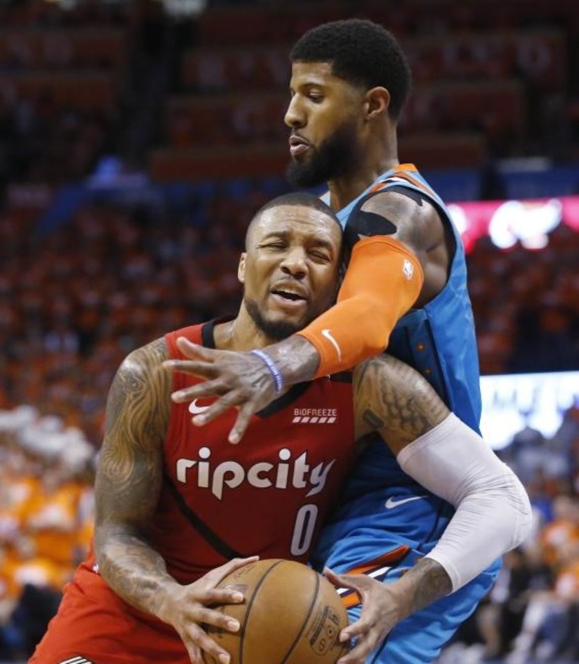 Photo - Portland Trail Blazers guard Damian Lillard (0) drives against Oklahoma City Thunder forward Paul George during the second half of Game 3 of an NBA basketball first-round playoff series Friday, April 19, 2019, in Oklahoma City. (AP Photo/Sue Ogrocki)