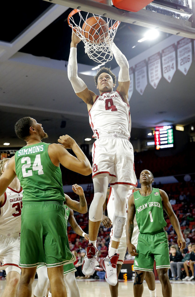 Photo - Oklahoma's Jamuni McNeace (4) dunks as North Texas' Zachary Simmons (24) and North Texas' Umoja Gibson (1) look on during the college men's basketball game between the University of Oklahoma and North Texas at the Lloyd Noble Center in Norman, Okla.,  Tuesday, Nov. 27, 2018.Photo by Sarah Phipps, The Oklahoman