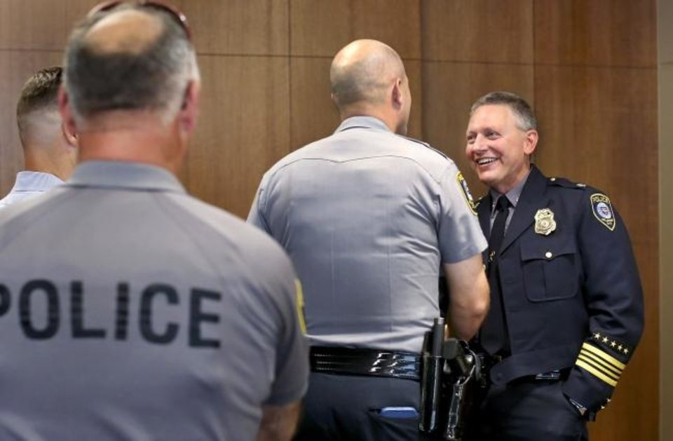Photo -  Officers line up to congratulate Wade Gourley, right, after he was named Oklahoma City police chief Monday by City Manager Craig Freeman. [Jim Beckel/The Oklahoman]