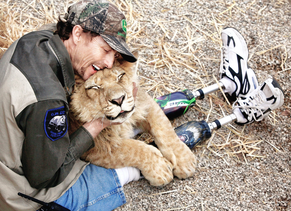 Photo - The park manager at the G.W. Exotic Animal Park, John Reinke, hugs the lion that he is trying to nurse back to health. Reinke said the lion is just learning to growl. Photo BY JIM BECKEL, THE OKLAHOMAN