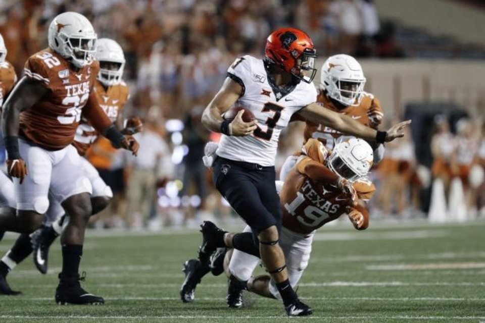 Photo -  Oklahoma State quarterback Spencer Sanders (3) scrambles past Texas defensive back Brandon Jones (19) during the first half Saturday. [AP Photo/Eric Gay]