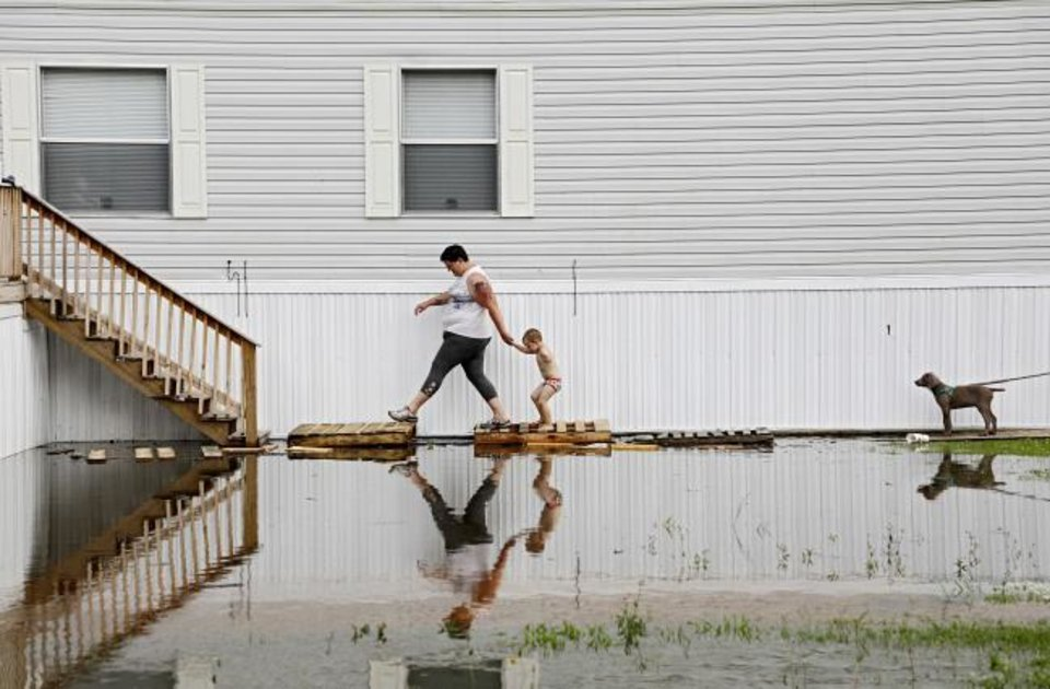 Photo -  Samantha Karnes and her son Anthony Pickett, 3, walk up to their neighbor's home to check on him as floodwaters from the Arkansas River approach at the Riverside Mobile Home Park in Muskogee. [Mike Simons/Tulsa World]
