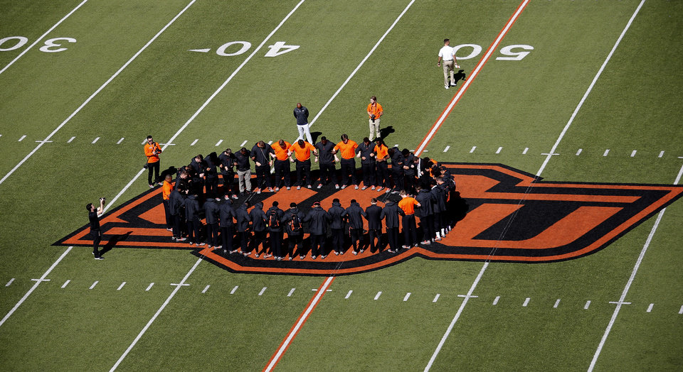Photo - Members of the Oklahoma State football team pray before the college football game between Oklahoma State University and Baylor at Boone Pickens Stadium in Stillwater, Okla., Saturday, Oct. 19, 2019. [Sarah Phipps/The Oklahoman]