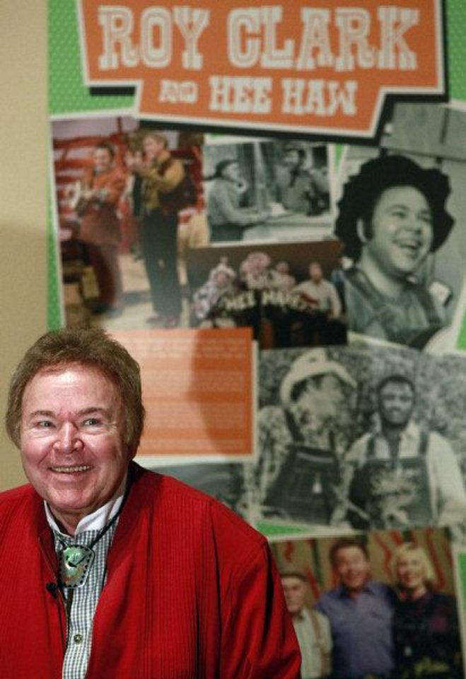 Photo - Roy Clark poses for a photograph as he sits in the new exhibit