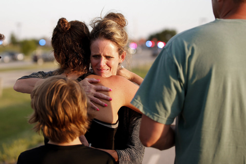 Photo - Jennifer Stong hugs Tasha Hunt outside the scene of a shooting on the east side of Lake Hefner in Oklahoma City, Thursday, May 24, 2018. Stong was inside the restaurant when the shooting occurred along with Hunt's children. Photo by Bryan Terry, The Oklahoman