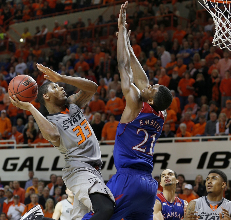 Photo - Oklahoma State's Marcus Smart (33) makes a basket in front of Kansas' Joel Embiid (21) in the final minutes of an NCAA college basketball game between Oklahoma State University (OSU) and the University of Kansas at Gallagher-Iba Arena in Stillwater, Okla., Saturday, March 1, 2014. Oklahoma State won 72-65. Photo by Bryan Terry, The Oklahoman