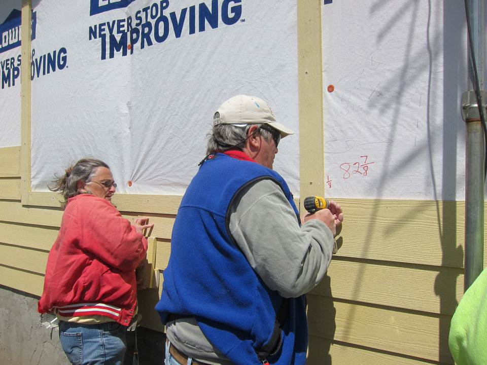 Photo -  Avis Norton, of Minnesota, and Tim Brubaker, of Harbor Springs, Mich., attach siding to a Newalla home as part of a Nomad project.  Photo by Carla Hinton, The Oklahoman