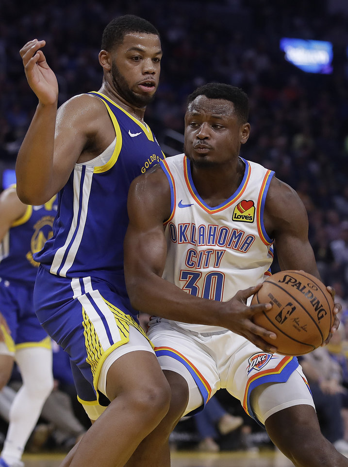 Photo - Golden State Warriors' Omari Spellman, left, defends against Oklahoma City Thunder guard Deonte Burton (30) in the first half of an NBA basketball game Monday, Nov. 25, 2019, in San Francisco. (AP Photo/Ben Margot)