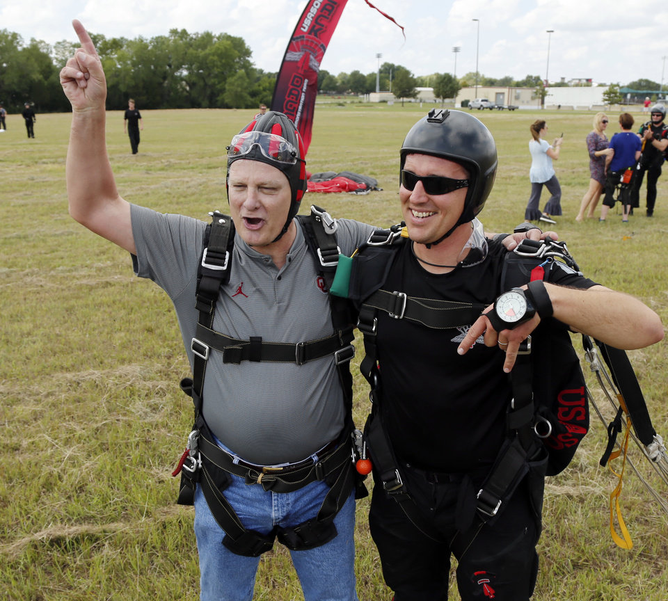 Photo - University of Oklahoma (OU) President Jim Gallogly, makes a tandem parachute jump with Sgt. 1st Class Sean O'Toole of the U.S. Army Special Operations Command Parachute Demonstration Team, the Army Black Daggers, as a warm-up to the OU versus Army football game on Thursday, Sept. 20, 2018 in Norman, Okla.  Photo by Steve Sisney, The Oklahoman