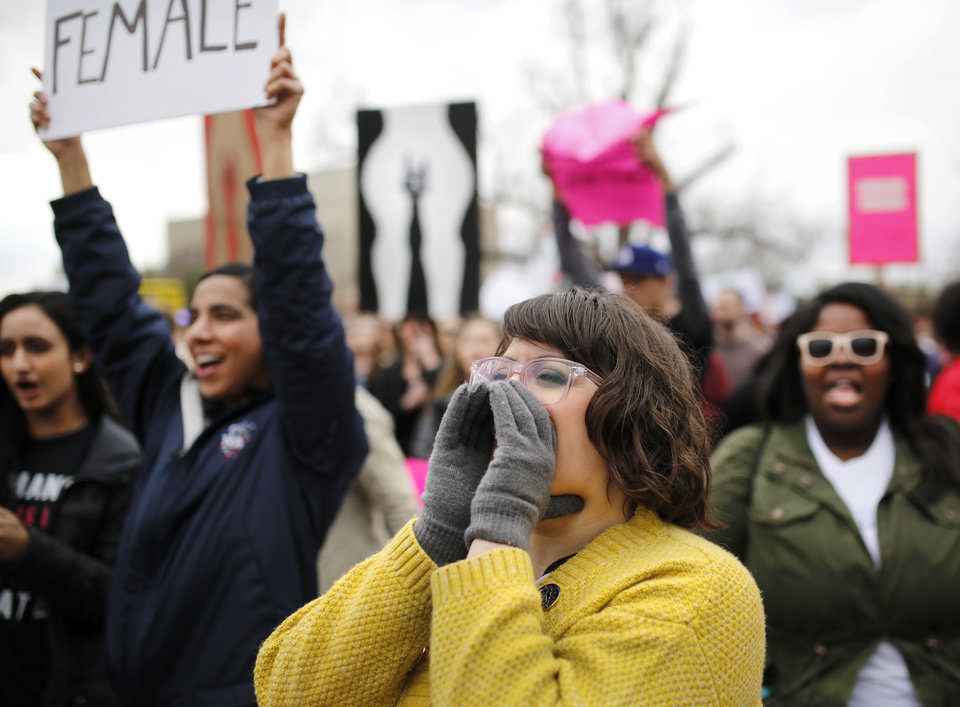 Photo - Members of the crowd show their approval for the comments made by one of the guest speakers at the rally. A crowd estimated by organizers to be as many as 7,000 people came to the state Capitol in Oklahoma City Saturday, Jan. 21, 2017, to rally, using their voices and signs to express displeasure with the nation's new administration as part of a larger network of marches taking place across the country following Donald Trump's inauguration.   The Women's March on Oklahoma included a walk along Lincoln Blvd., with the Capitol as a backdrop, and a rally on the Capitol's south plaza that featured nearly a dozen speakers.  Photo by Jim Beckel, The Oklahoman