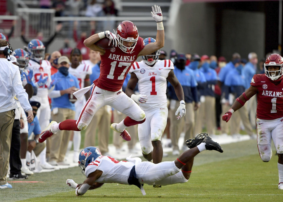 Photo -  Arkansas defensive back Hudson Clark (17) leaps over Mississippi running back Tylan Knight (4) as he returns an interception during the second half of a 33-21 win Saturday in Fayetteville, Ark. [Michael Woods/the associated press]