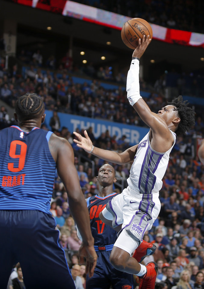 Photo - Sacramento's De'Aaron Fox (5) puts up a shot beside Oklahoma City's Dennis Schroder (17) during an NBA basketball game between the Oklahoma City Thunder and the Sacramento Kings at Chesapeake Energy Arena in Oklahoma City, Sunday, Oct. 21, 2018. Photo by Bryan Terry, The Oklahoman