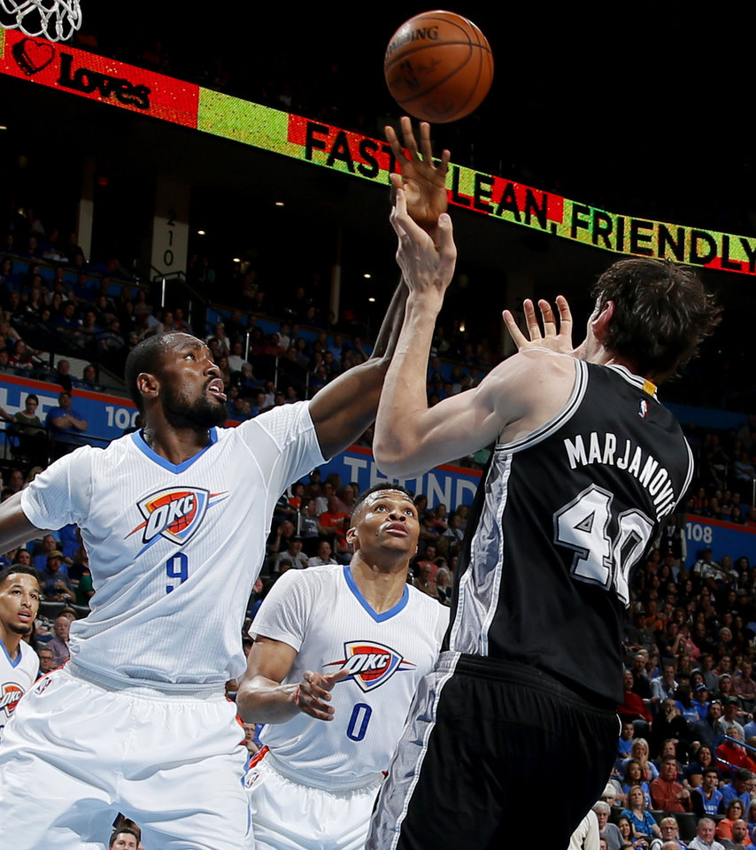 Photo - Oklahoma City's Serge Ibaka (9) and Russell Westbrook (0) defend San Antonio's Boban Marjanovic (40) during an NBA basketball game between the Oklahoma City Thunder and the San Antonio Spurs at Chesapeake Energy Arena in Oklahoma City, Saturday, March 26, 2016. Photo by Bryan Terry, The Oklahoman