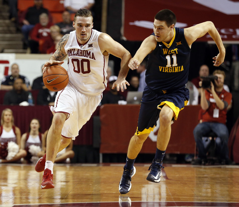 Photo - Oklahoma's Ryan Spangler (00) brings the ball down court guarded by West Virginia's Nathan Adrian (11) as the University of Oklahoma Sooner (OU) men play the West Virginia Mountaineers (WV) in NCAA, college basketball at The Lloyd Noble Center on Jan. 16, 2016 in Norman, Okla. Photo by Steve Sisney, The Oklahoman