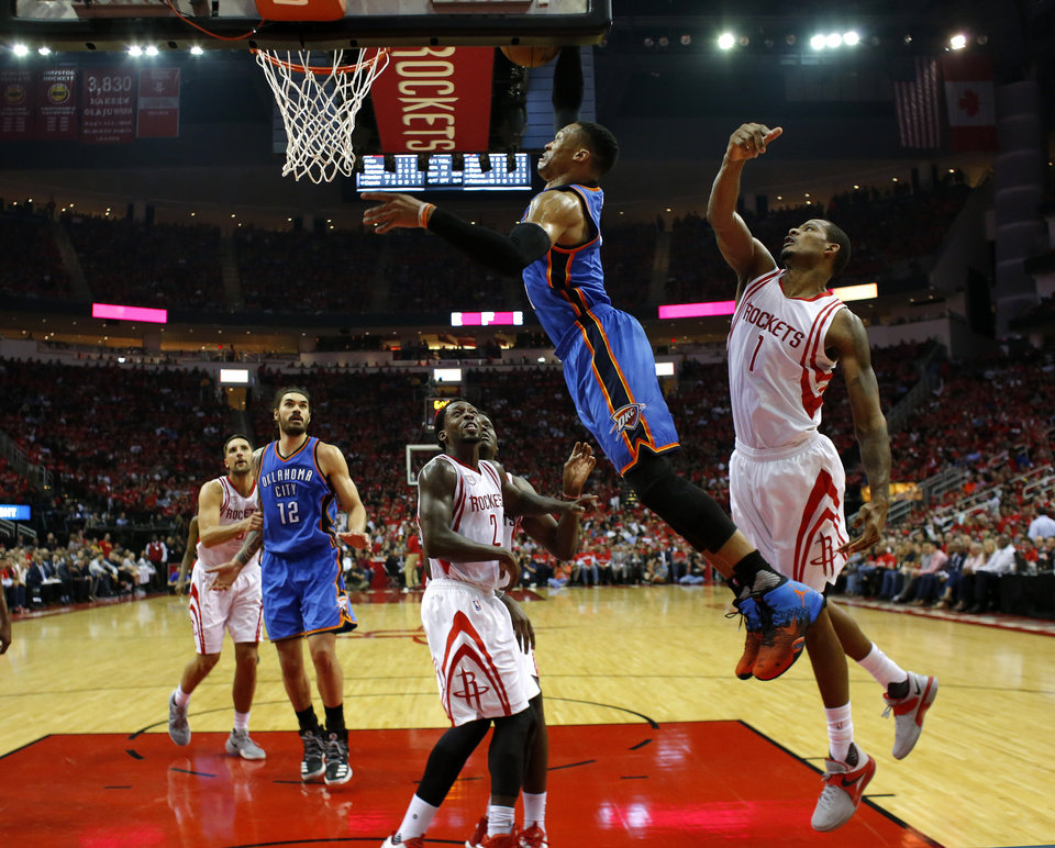 Photo - Oklahoma City's Russell Westbrook (0) goes to the basket as Houston's Trevor Ariza (1) defneds during Game 2 in the first round of the NBA playoffs between the Oklahoma City Thunder and the Houston Rockets in Houston, Texas,  Wednesday, April 19, 2017.  Photo by Sarah Phipps, The Oklahoman