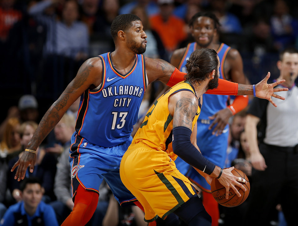 Photo - Oklahoma City's Paul George (13) defends against Utah's Ricky Rubio (3) during the NBA game between the Oklahoma City Thunder and the Utah Jazz at the Chesapeake Energy Arena, Friday, Feb. 22, 2019. Photo by Sarah Phipps, The Oklahoman