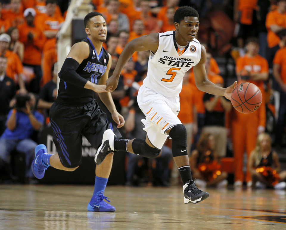 Photo - Oklahoma State's Stevie Clark (5) goes past Memphis' Michael Dixon Jr. (11) during an NCAA college basketball game between Oklahoma State and Memphis at Gallagher-Iba Arena in Stillwater, Okla., Tuesday, Nov. 19, 2013. Photo by Bryan Terry, The Oklahoman