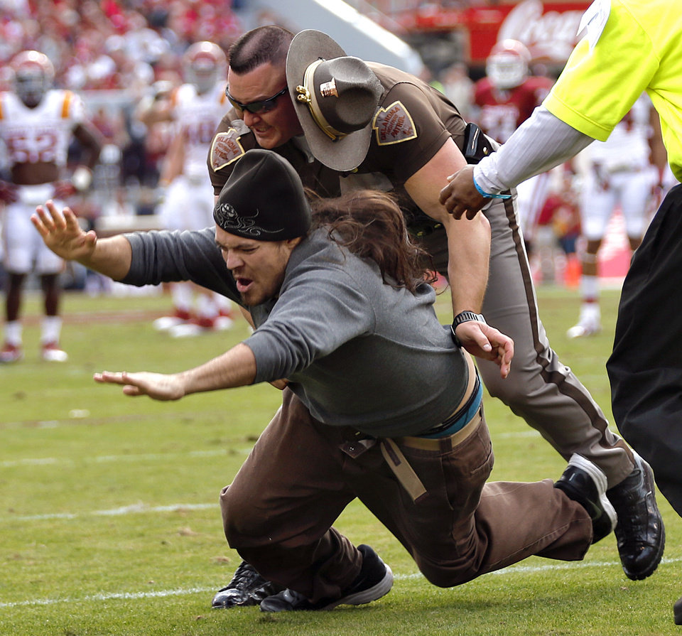 Photo -  An Oklahoma Highway Patrol trooper, Brian Orr, tackles a fan who ran on to the field in Norman in 2013 during the University of Oklahoma's game against Iowa State. [Photo by Chris Landsberger, The Oklahoman Archives]