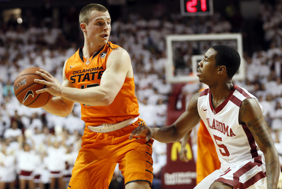Photo - Oklahoma State's Phil Forte (13) holds the ball as Oklahoma's Je'lon Hornbeak (5) defends in the first half during the NCAA men's Bedlam basketball game between the Oklahoma State Cowboys (OSU) and the Oklahoma Sooners (OU) at Lloyd Noble Center in Norman, Okla., Monday, Jan. 27, 2014. Photo by Nate Billings, The Oklahoman