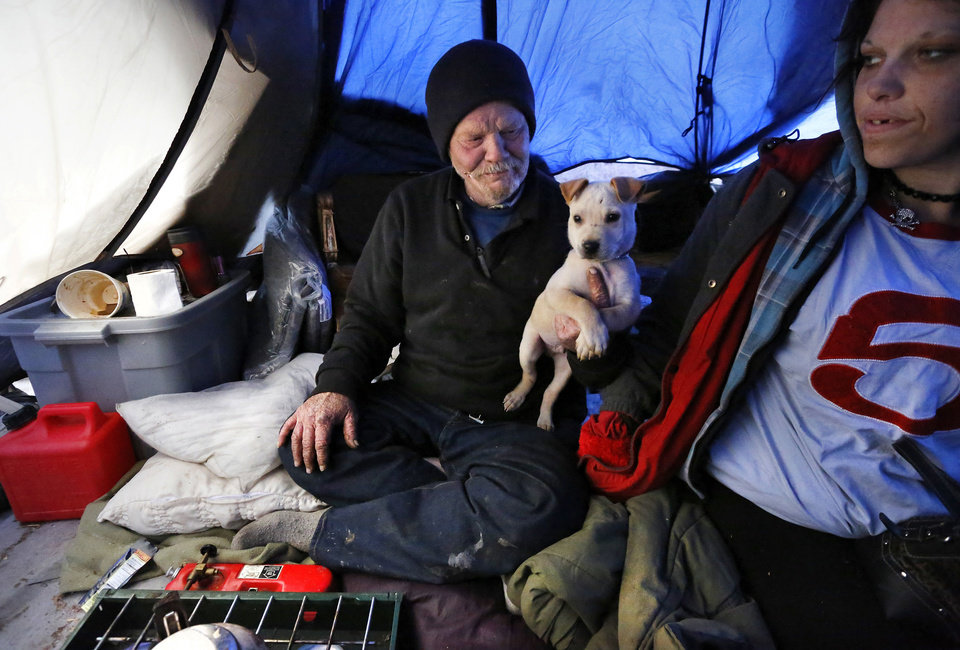 Photo - Jackson Poadger, 53, his dog and three other adults were huddled inside his tent at a homeless encampment hidden by trees near MainStreet and Villa. In preparation for this week's winter storms,  homeless shelters and organizations are ramping up efforts to house people during the coldest days the state has seen in several years. This includes actively going out to documented homeless camps and trying to convince people to accept a ride to an indoor shelter in Oklahoma City, but not everyone agrees to abandon their camps, some out of a fear that their material possessions will be stolen while they're gone.  Jonathon Roberts, with Be the Change, an Oklahoma City based non-profit that provides assistance to the homeless, gave Poadger and his friends extra blankets when he  checked on a number of encampments west of the downtown area Thursday afternoon, Dec. 5, 2013. Photo by Jim Beckel, The Oklahoman  Jim Beckel - THE OKLAHOMAN