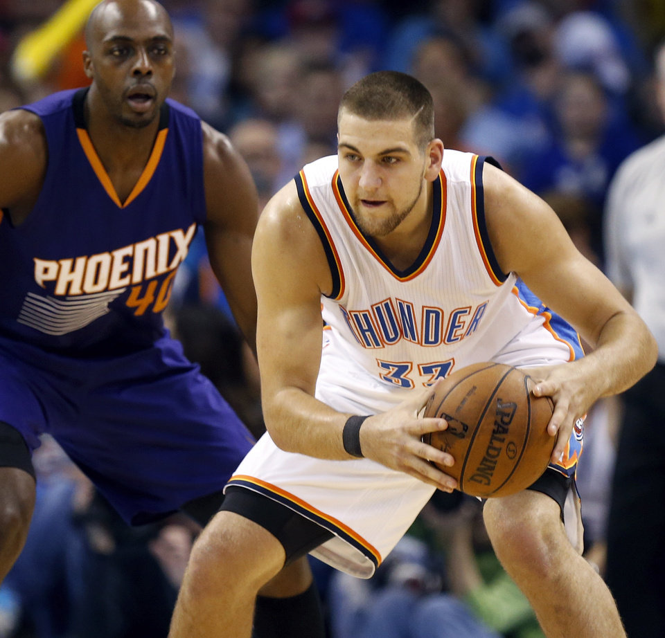 Photo - Oklahoma City's Mitch McGary (33) holds the ball in front of Phoenix's Anthony Tolliver (40) during an NBA basketball game between the Phoenix Suns and the Oklahoma City Thunder at Chesapeake Energy Arena in Oklahoma City, Sunday, Dec. 14, 2014. Oklahoma City won 112-88. PHOTO BY NATE BILLINGS, The Oklahoman