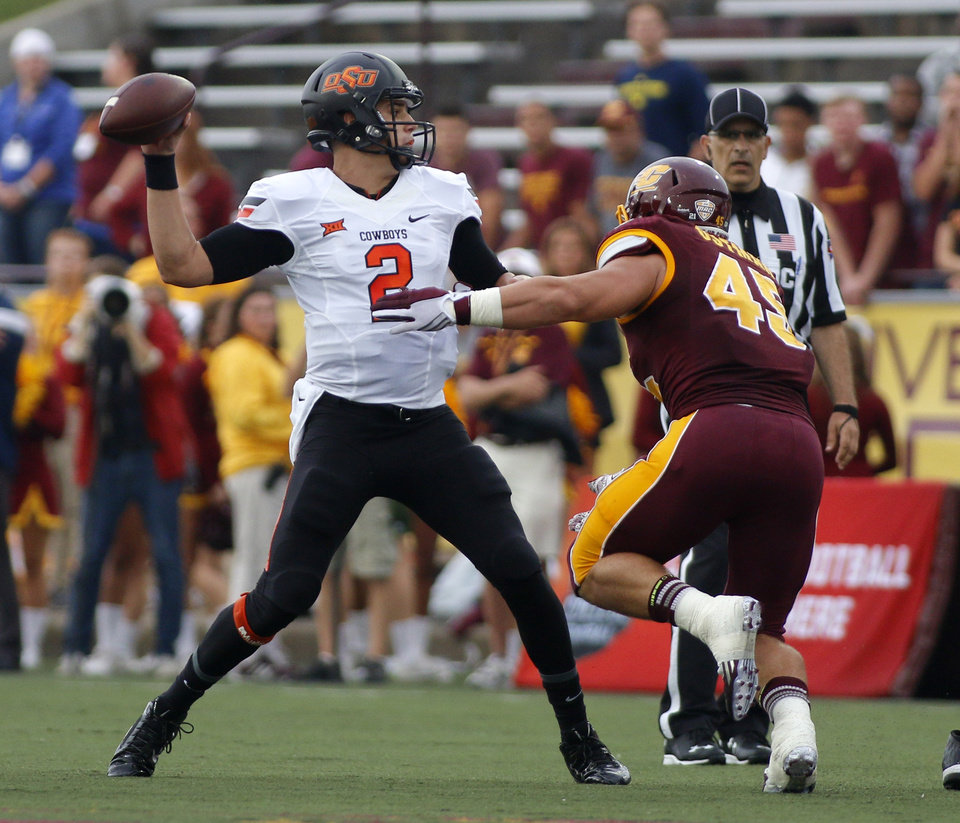 Photo - Oklahoma State quarterback Mason Rudolph (2) throws a pass against Central Michigan's Joe Ostman (45) during the first quarter of an NCAA college football game, Thursday, Sept. 3, 2015, in Mount Pleasant, Mich.  Oklahoma State won 24-13. (AP Photo/Al Goldis)