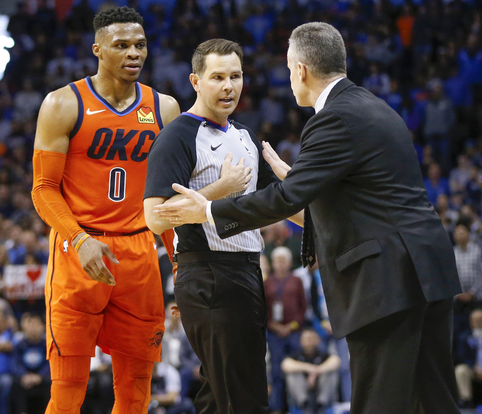 Photo - Oklahoma City head coach Billy Donovan, right, and Russell Westbrook (0) talk to official Brian Forte after Westbrook was called for a foul after colliding with Dallas' Jalen Brunson (13), not pictured, as they chased the ball in the fourth quarter of an NBA basketball game between the Dallas Mavericks and the Oklahoma City Thunder at Chesapeake Energy Arena in Oklahoma City, Sunday, March 31, 2019. Dallas won 106-103. Photo by Nate Billings, The Oklahoman
