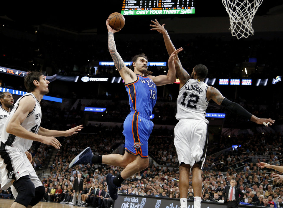Photo - Oklahoma City's Steven Adams (12) dunks the ball from between San Antonio's Boban Marjanovic (40) and LaMarcus Aldridge (12) during Game 2 of the second-round series between the Oklahoma City Thunder and the San Antonio Spurs in the NBA playoffs at the AT&T Center in San Antonio, Monday, May 2, 2016. Photo by Bryan Terry, The Oklahoman