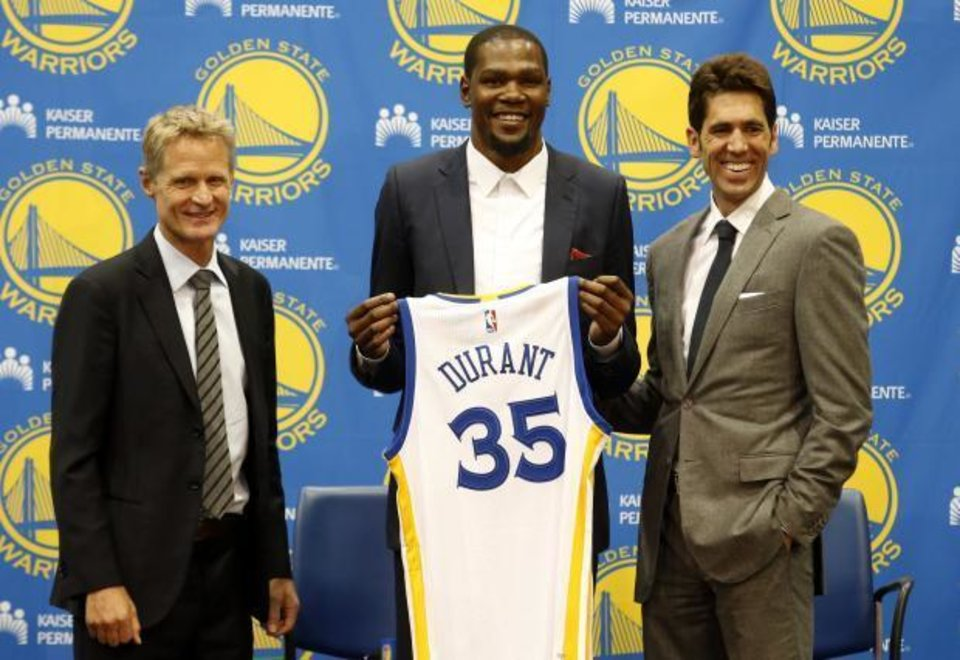 Photo - Golden State Warriors' newest player Kevin Durant, center, joins head coach Steve Kerr, left and general manager Bob Myers during a news conference at the NBA basketball team's practice facility, Thursday, July 7, 2016, in Oakland, Calif. (AP Photo/Beck Diefenbach)