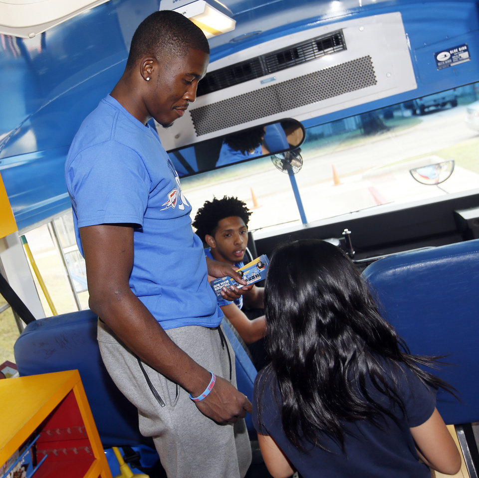 Photo - Oklahoma City guards Semaj Christon, front, and Cameron Payne talk to a student after she picked out a free book during a stop by the Oklahoma City Thunder's Rolling Thunder Book Bus at Sequoyah Elementary on  Thursday. (Photo by Nate Billings, The Oklahoman)