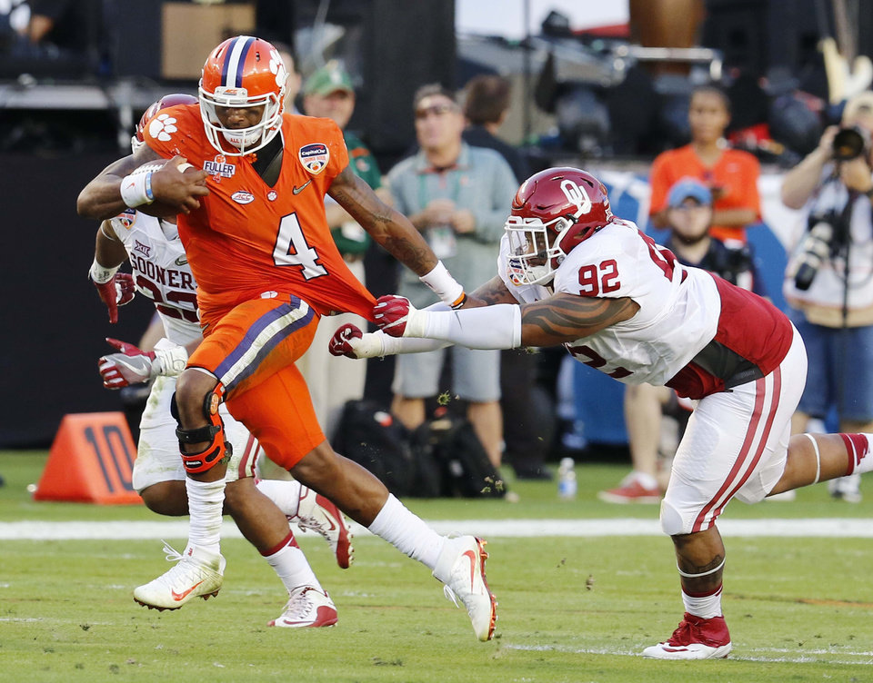 Photo - Clemson quarterback Deshaun Watson (4) runs with the ball as Oklahoma defensive tackle Matthew Romar (92) attempts to stop him, during the first half of the Orange Bowl NCAA college football semifinal playoff game, Thursday, Dec. 31, 2015, in Miami Gardens, Fla. (AP Photo/Joe Skipper)