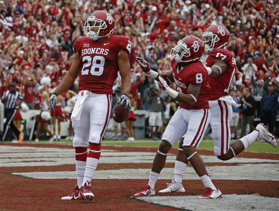Photo - Oklahoma's Alex Ross (28) celebrates after returning a kickoff for a touchdown in front of Austin Bennett (8) and Jordan Smallwood (17) during the Red River Showdown college football game between the University of Oklahoma Sooners (OU) and the University of Texas Longhorns (UT) at the Cotton Bowl in Dallas on Saturday, Oct. 11, 2014. 