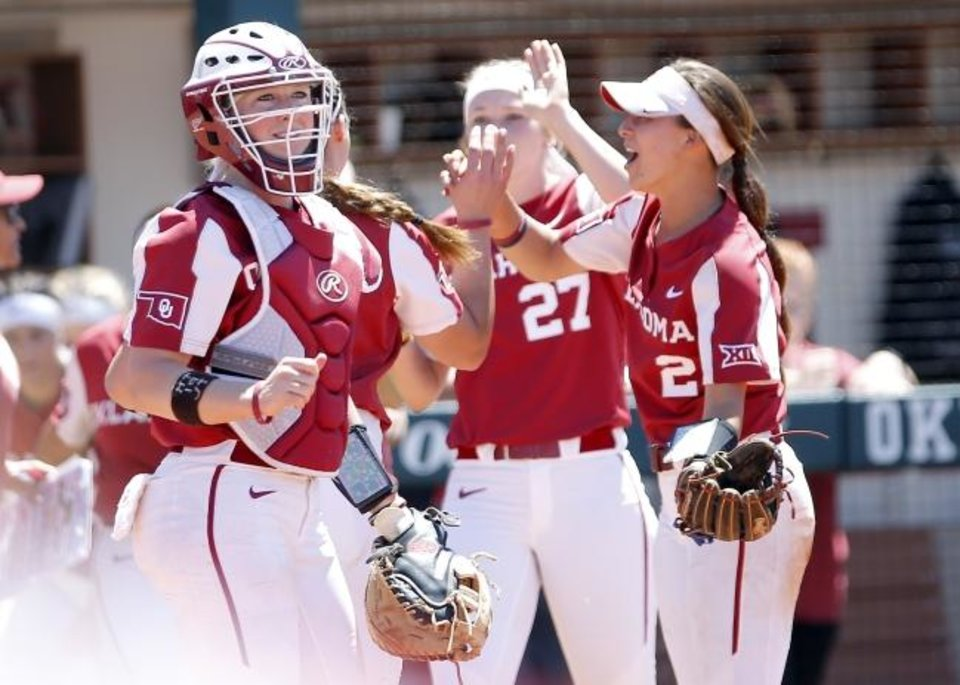 Photo - Oklahoma's Lynnsie Elam (22) celebrates with teammates after an out during college softball game between Oklahoma and Wisconsin in the NCAA Norman Regional at Marita Hynes Field in Norman, Okla., Sunday, May 19, 2019. OU won 2-0. Photo by Sarah Phipps, The Oklahoman