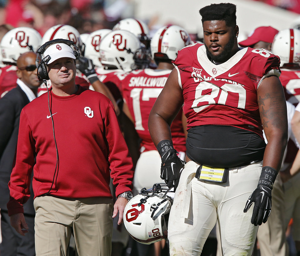Photo - Bob Stoops and Jordan Phillips (80) walk the sidelines during the college football game between the University of Oklahoma Sooners (OU) and The Baylor University Bears (BU) at Gaylord Family-Oklahoma Memorial Stadium in Norman, Okla. on Saturday, Nov. 8, 2014.  Photo by Chris Landsberger, The Oklahoman