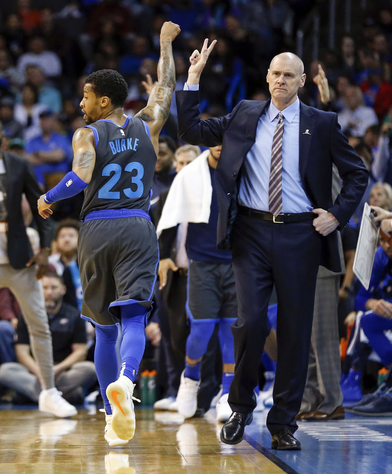 Photo - Dallas' Trey Burke (23) and coach Rick Carlisle high five after Burke hit a three-point shot in the final seconds of the third quarter during an NBA basketball game between the Dallas Mavericks and the Oklahoma City Thunder at Chesapeake Energy Arena in Oklahoma City, Sunday, March 31, 2019. Dallas won 106-103. Photo by Nate Billings, The Oklahoman