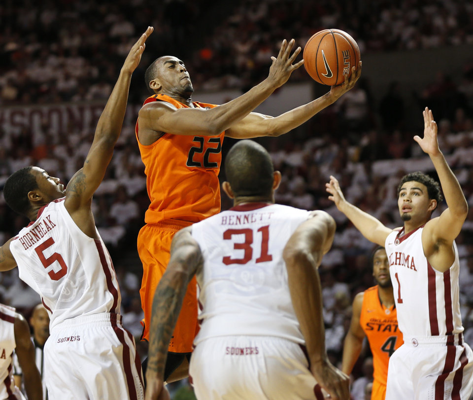 Photo - Oklahoma State's Markel Brown (22) takes the ball to the hoop between Oklahoma's Je'lon Hornbeak (5), D.J. Bennett (31) and Frank Booker (1) in the first half during the NCAA men's Bedlam basketball game between the Oklahoma State Cowboys (OSU) and the Oklahoma Sooners (OU) at Lloyd Noble Center in Norman, Okla., Monday, Jan. 27, 2014. Photo by Nate Billings, The Oklahoman