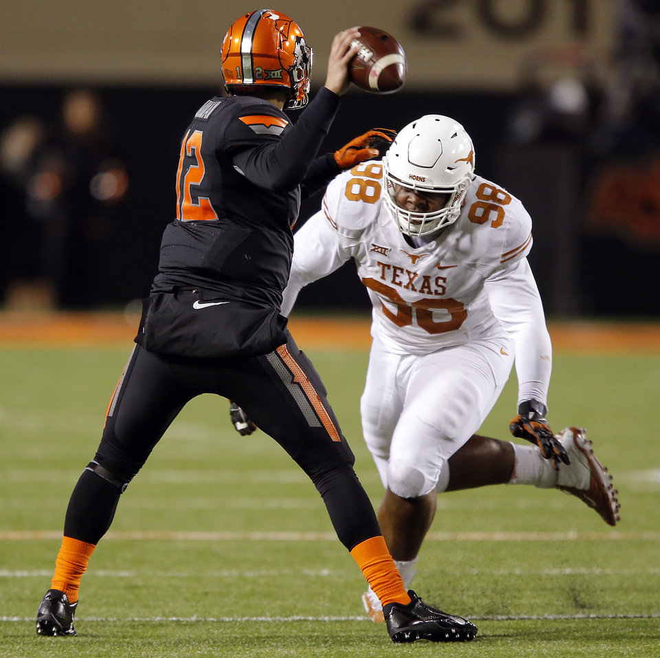 Photo - Texas' Hassan Ridgeway (98) puts pressure on Oklahoma State's Daxx Garman (12) as he throws the ball during the college football game between the Oklahoma State University Cowboys (OSU) the University of Texas Longhorns (UT) at Boone Pickens Staduim in Stillwater, Okla. on Saturday, Nov. 15, 2014.  Photo by Chris Landsberger, The Oklahoman
